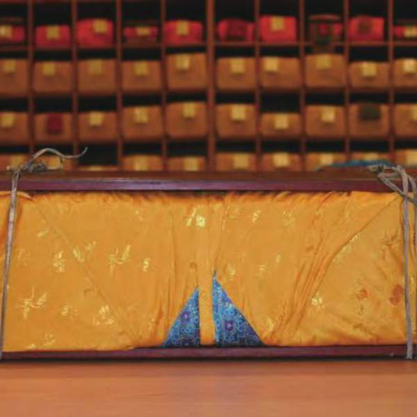 Mongolian Tanjur wrapped in yellow fabric and protected by sandalwood boards <br />